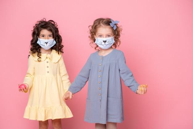 Duas garotas em máscara protetora com ovos coloridos de mãos dadas no fundo rosa. covid conceito de páscoa.