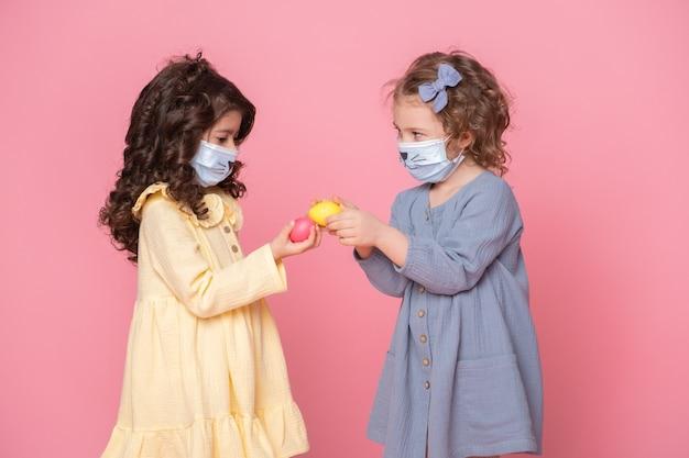 Duas garotas em máscara protetora com ovos coloridos em fundo rosa. covid conceito de páscoa.