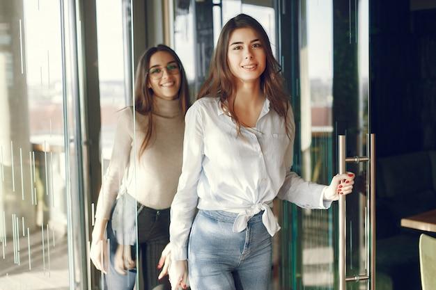Duas garotas em pé no café