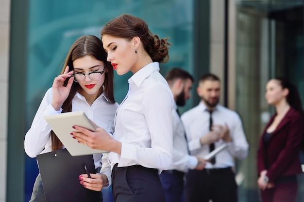 Duas garotas em roupas de estilo de escritório na construção de plano de fundo