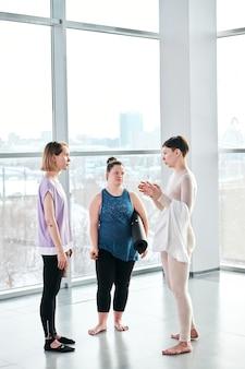 Duas garotas em roupas esportivas, ouvindo o que o instrutor de fitness ou ioga está dizendo e fazendo perguntas após o treino na academia