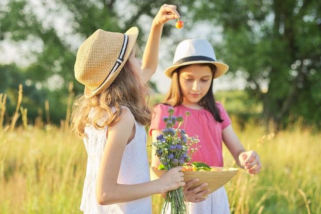 Duas garotas em um dia ensolarado de verão em um prado com uma tigela de frutas doces