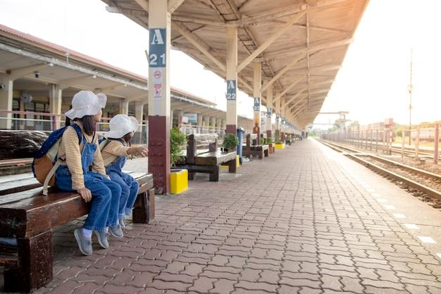 Duas garotas em uma estação ferroviária, esperando o trem