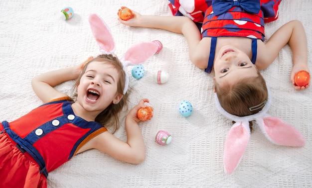 Duas garotas engraçadas bonitos com ovos de páscoa e orelhas de coelho em um lindo vestido brilhante.
