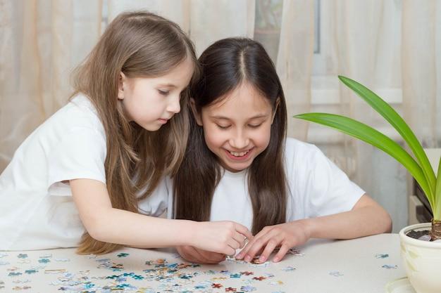 Duas garotas engraçadas brincando juntas, sentadas em uma mesa perto da janela e colecionando quebra-cabeças