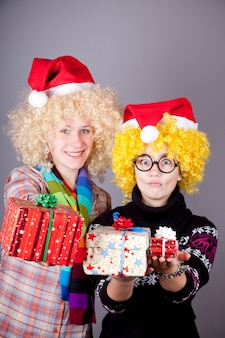 Duas garotas engraçadas com presentes de natal. tiro do estúdio.