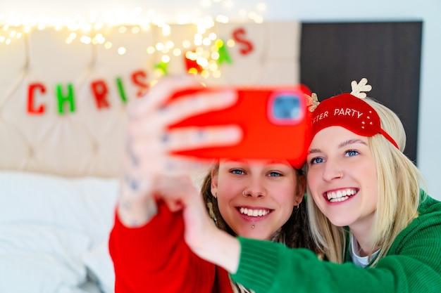 Duas garotas engraçadas em suéteres de natal tiram selfies. foto de alta qualidade