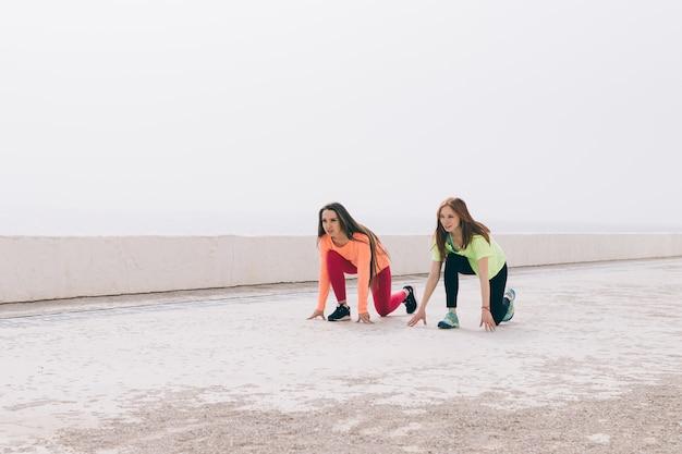 Duas garotas esbeltas no sportswear estão se preparando para correr ao longo da praia