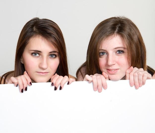 Duas garotas espreitam de um painel branco