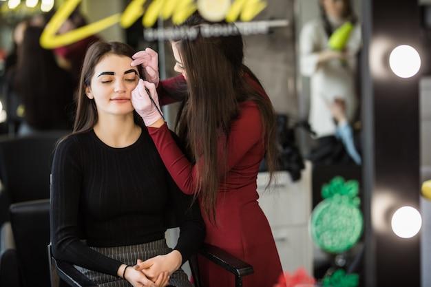Duas garotas estão fazendo maquiagem na frente do grande espelho profissional