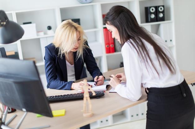 Duas garotas estão no escritório curvadas perto da mesa e trabalham com documentos.