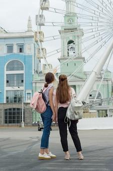 Duas garotas estão olhando para a roda gigante