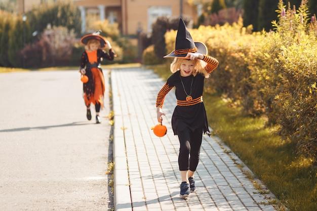 Duas garotas estão se divertindo brincando de doce ou travessura no halloween ao ar livre no outono, as crianças estão vestindo ...