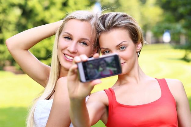 Duas garotas estão tirando fotos de si mesmas