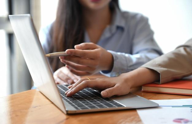 Duas garotas estão usando um laptop.