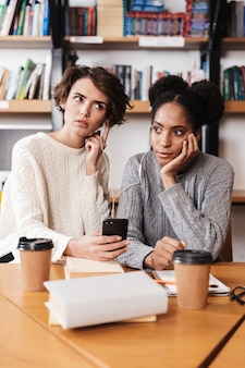 Duas garotas estudando na biblioteca, ouvindo música com fones de ouvido