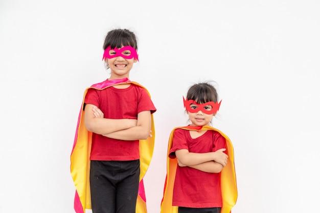 Duas garotas fantasiadas de super-heróis em fundo branco