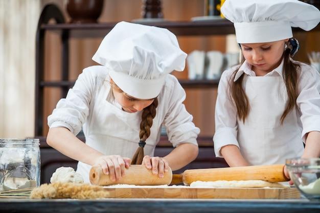 Duas garotas fazem massa de farinha.