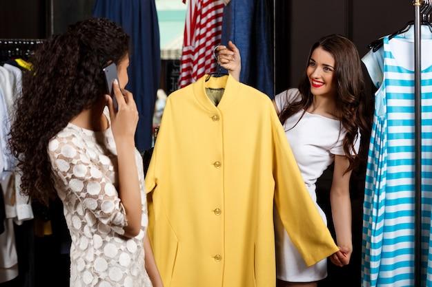 Duas garotas fazendo compras no shopping. um falando no telefone.
