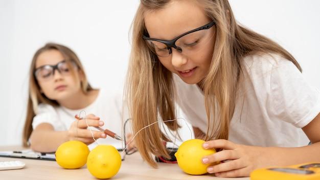 Duas garotas fazendo experimentos científicos com eletricidade e limões