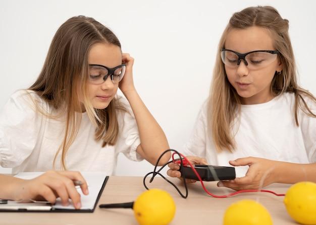 Duas garotas fazendo experimentos científicos com limões e eletricidade