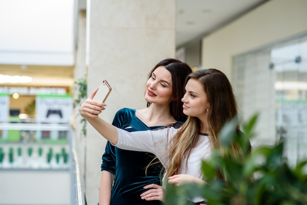 Duas garotas fazendo selfi na loja.