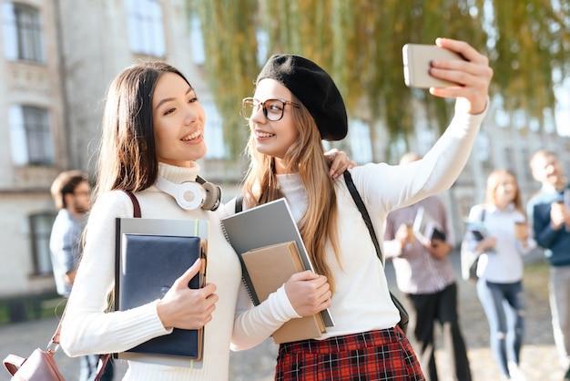 Duas garotas fazendo selfie no pátio da universidade.