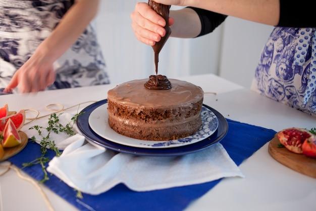 Duas garotas fazendo um bolo na cozinha. feminino mão aperta o creme de chocolate