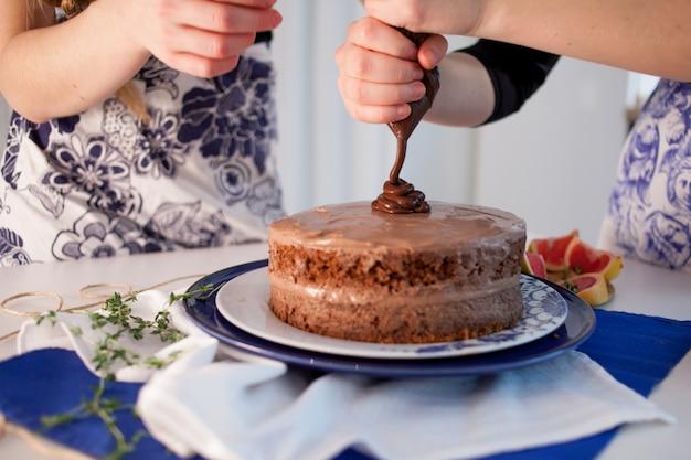 Duas garotas fazendo um bolo na cozinha