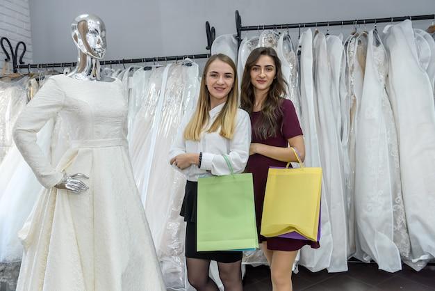 Duas garotas felizes com sacolas de compras no salão de casamento