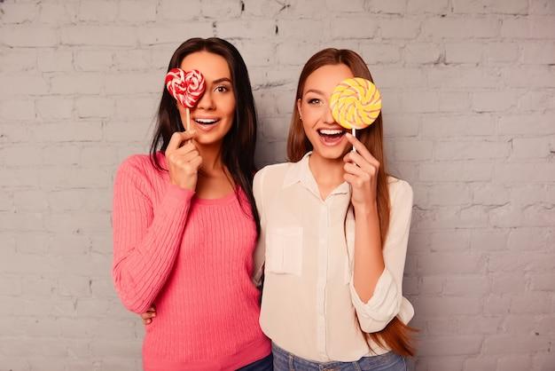 Duas garotas felizes se alegrando com um pirulito e sorrindo