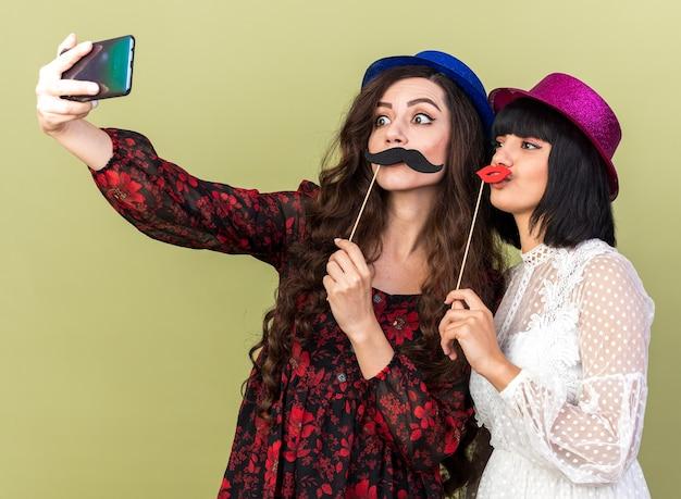 Duas garotas festeiras com chapéu de festa, ambas segurando bigode falso e lábios no palito na frente dos lábios, tirando selfie juntas, isoladas na parede verde oliva
