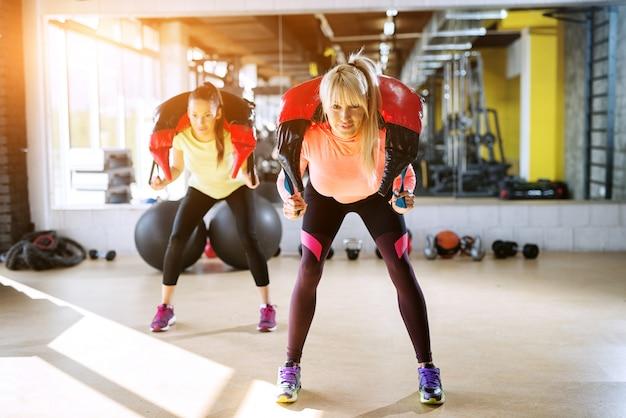 Duas garotas focadas em forma fazendo agachamentos com equipamentos de musculação em volta do pescoço.