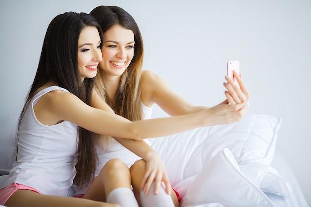Duas garotas gostosas, deitado em uma cama, tirando uma foto de si mesmas