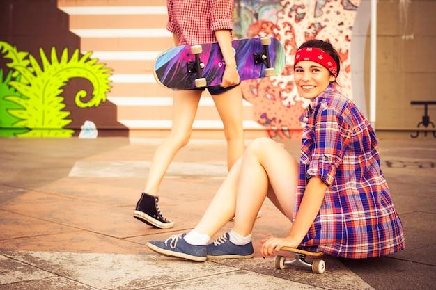 Duas garotas hipster adolescentes em skates