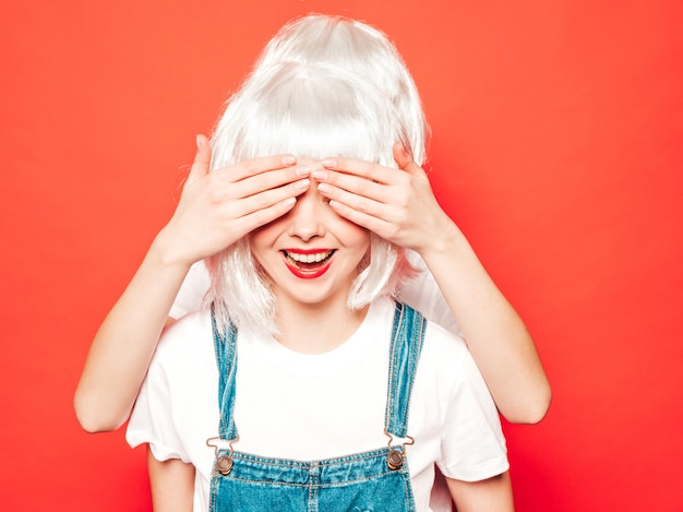 Duas garotas hipster sexy jovem em perucas brancas e lábios vermelhos. belas mulheres na moda em roupas de verão. modelos despreocupados posando perto da parede vermelha no estúdio. cobrindo os olhos dela e abraçando por trás