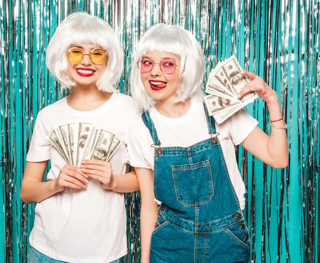 Duas garotas hipster sexy jovem em perucas brancas e lábios vermelhos. mulheres bonitas segurando dólares no verão de mãos gastar dinheiro