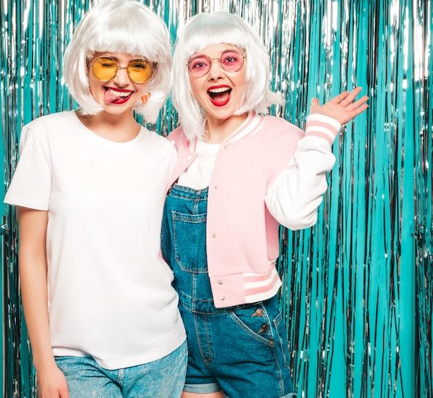 Duas garotas hipster sexy jovem em perucas brancas e lábios vermelhos. mulheres na moda bonitas no verão de roupas de verão em óculos de sol