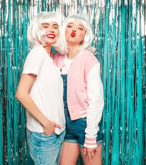Duas garotas hipster sexy jovem em perucas brancas e lábios vermelhos. mulheres na moda bonitas no verão de roupas de verão se divertindo