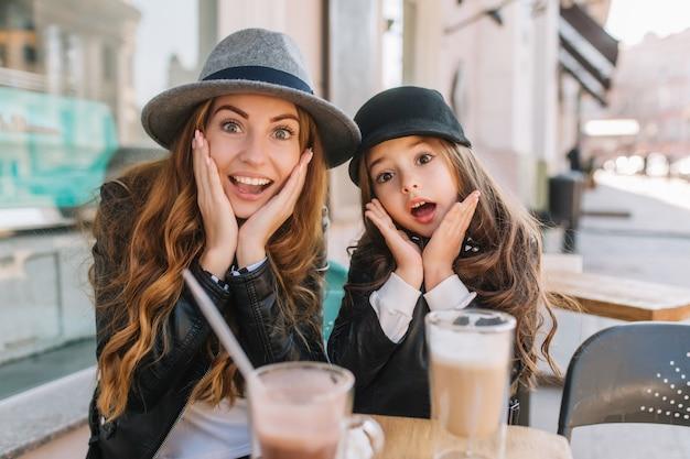 Duas garotas incríveis em chapéus da moda, posando com uma expressão careta durante o almoço em um restaurante de rua em um dia ensolarado.