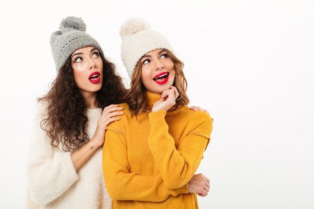 Duas garotas intrigadas em suéteres e chapéus juntos enquanto olhando para longe sobre parede branca