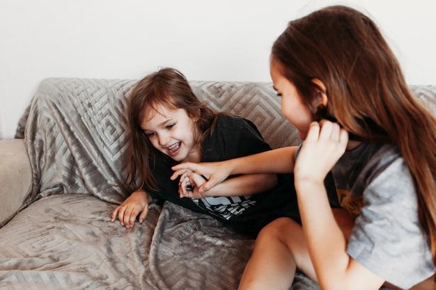 Duas garotas, irmãs brincando no sofá, abraços, risos, luta, camiseta