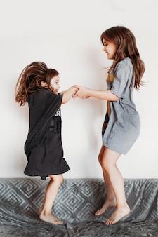 Duas garotas, irmãs, de mãos dadas e pulando no sofá, rindo, conversando