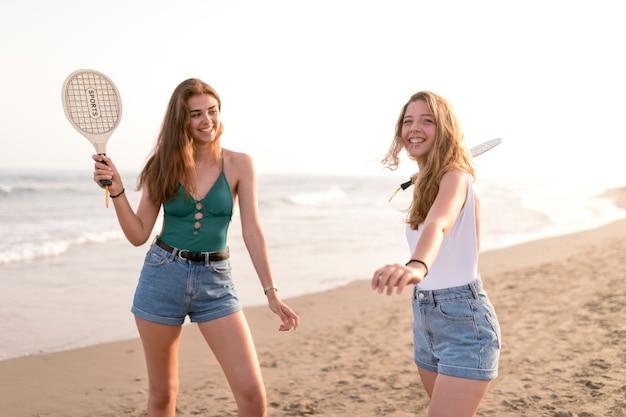 Duas garotas jogando tênis de praia perto da beira-mar