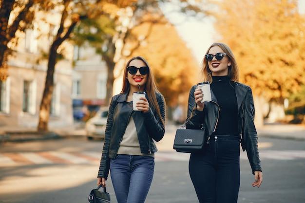 Duas garotas jovens e bonitas andando em uma cidade de verão