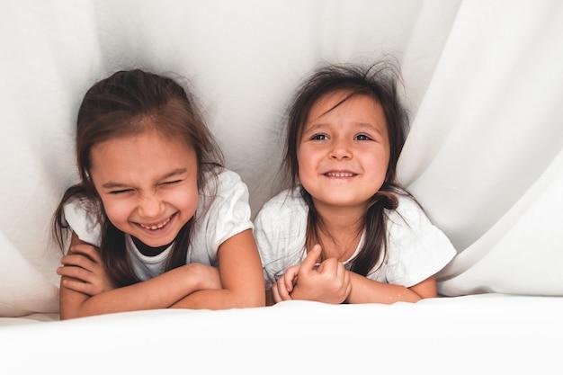 Duas garotas lendo embaixo do cobertor