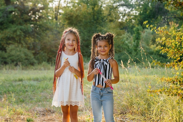 Duas garotas lindas com rabo de cavalo brincando no parque explodindo bolhas
