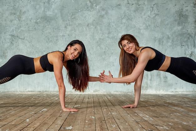 Duas garotas lindas e fitness fazendo exercícios na sala de fitness dão cinco. esporte de conceito, trabalho em equipe.