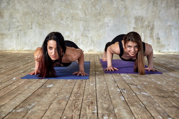 Duas garotas lindas e fitness fazendo exercícios na sala de fitness dão cinco.