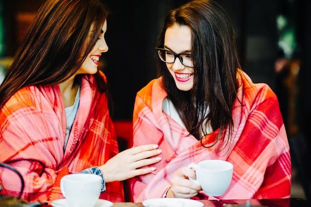 Duas garotas lindas fofocando no terraço com uma xícara de café